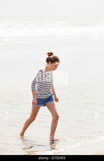 Girl wading in the water at beach - Stock Image
