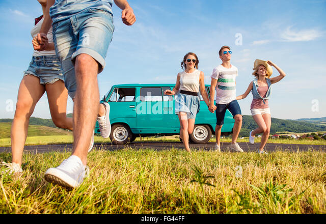 Running teenage couples in love outside against blue sky - Stock Image