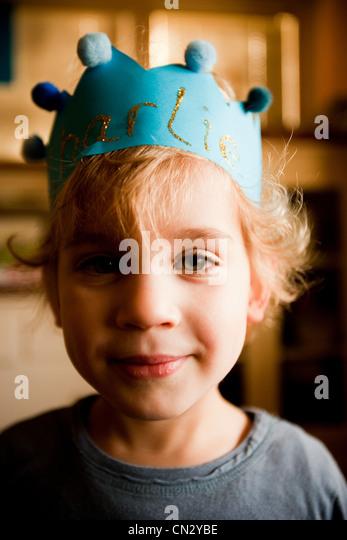 Boy wearing paper crown - Stock Image