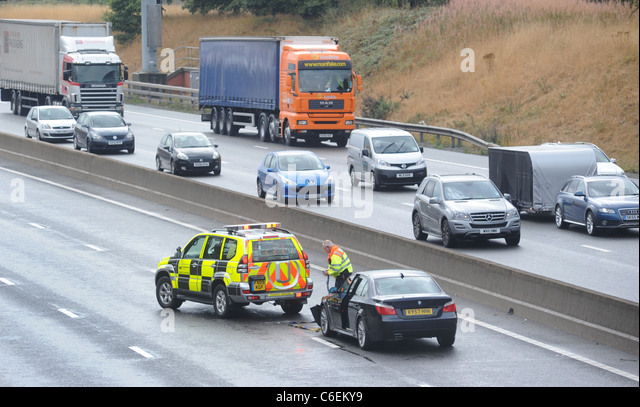 A HIGHWAYS AGENCY TRAFFIC OFFICER  ATTENDS TO A  STRANDED MOTORIST  IN THE FAST LANE OF THE M6 MOTORWAY  FOLLOWING - Stock Image