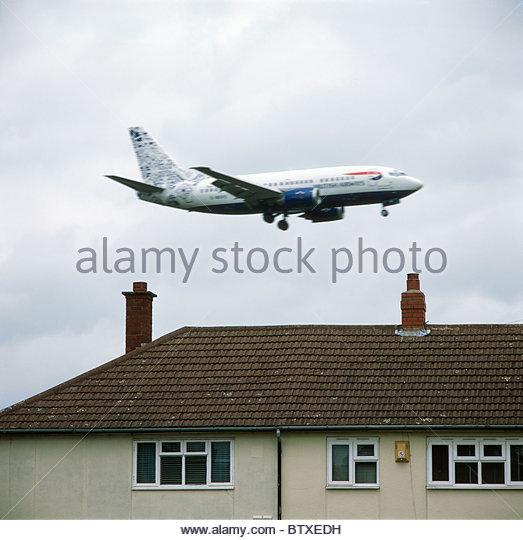 British Airways passenger plane landing at Birmingham Airport passing close to housing estate. Birmingham, UK. - Stock Image