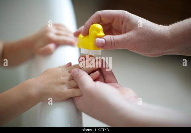 parent's hand cleaning kid's fingernail at the edge of bathtub. childhood, hands, nail brush, duck. - Stock-Bilder