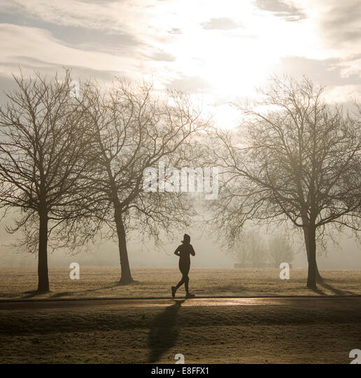 Silhouette of a woman Running through the park, England, UK - Stock Image