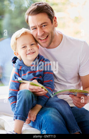 Father reading book to children - Stock Image