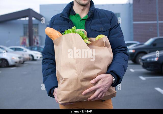 closeup of man holding a shopping bag - Stock Image