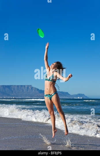 Young woman wearing a swimming costume jumping to catch a frisbee in the shallow waves. Table Mountain in background - Stock Image