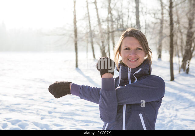 Young woman stretching in snow - Stock Image