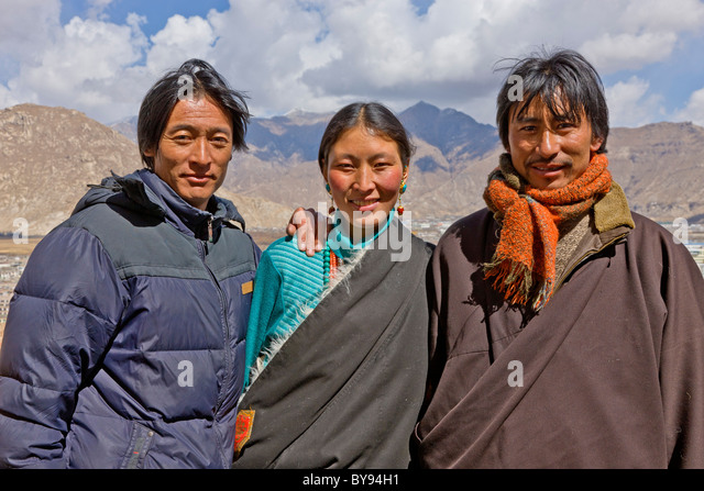 Tibetan wife with her two husbands nomadic pilgrims outside the Potala Palace Lhasa Tibet. JMH4577 - Stock Image