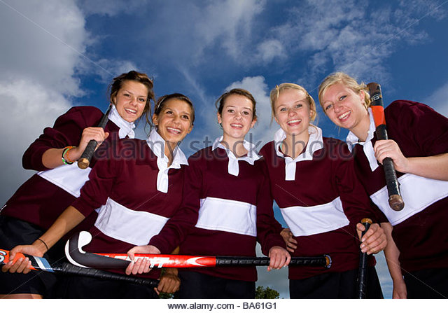 Portrait of smiling teenage girls holding field hockey sticks - Stock Image