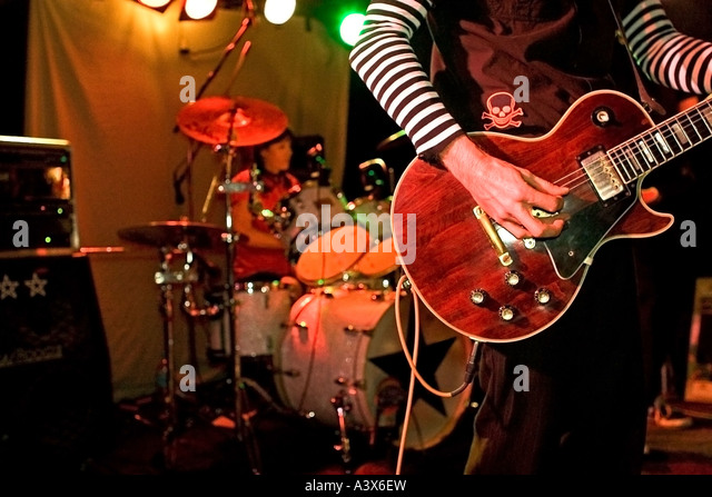 Close Up of Rock and Roll Guitarist on Stage with Drummer in the Background. - Stock Image