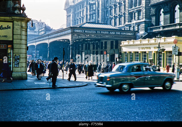 A rare look back into 1950s London as an Austin Westminster 6 cylinder drives past a busy Victoria Station. Image - Stock Image