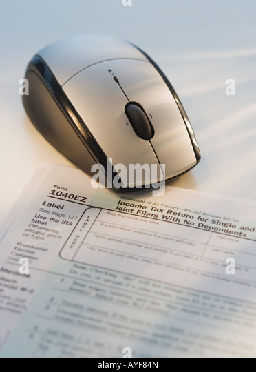 Computer mouse next to tax form - Stock Image