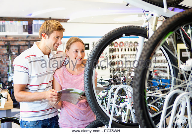 Couple choosing a bicycle in shop - Stock Image