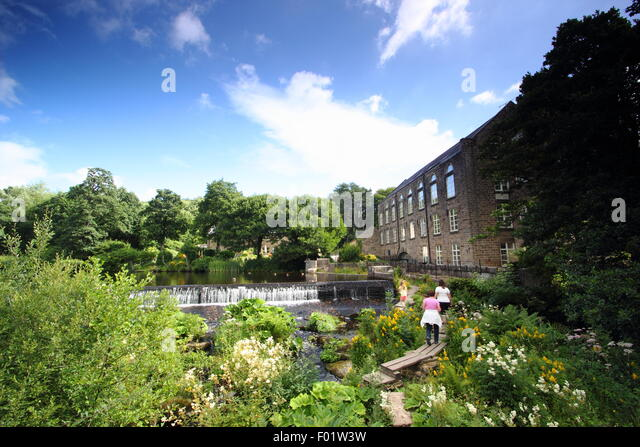 People cross the public footbridge across the River Derwent by Bamford Mill and weir in the Peak District National - Stock Image