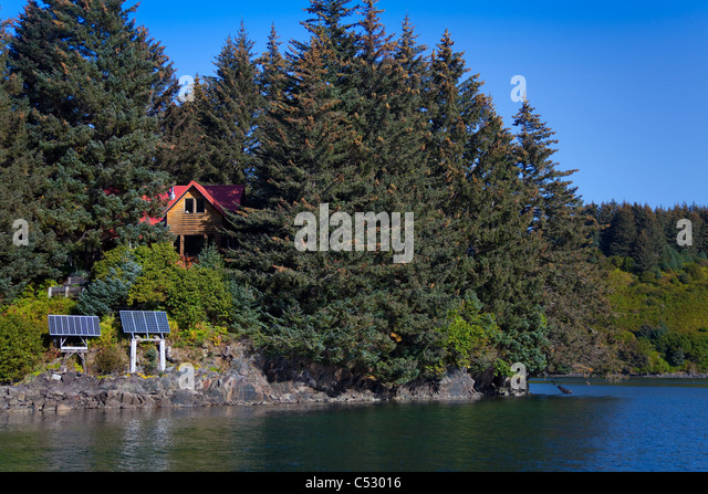 Scenic view of a log home powered by solar panels in Anton Larsen Bay, Kodiak Island, Southwest Alaska, Summer - Stock Image