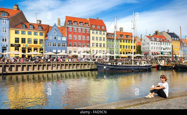 Copenhagen, Denmark - woman relaxing at Nyhavn Canal - Stock Image