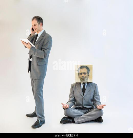 Businessman imagining self image of meditating while multitasking - Stock Image