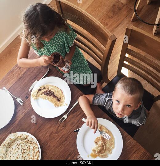 Little boy and little girl eating breakfast - Stock Image