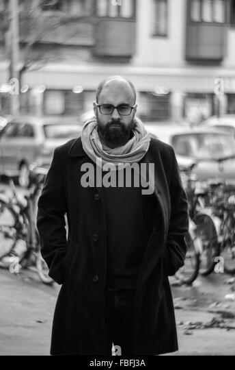 Portrait Of Serious Man Wearing Coat Standing With Hands In Pocket - Stock Image