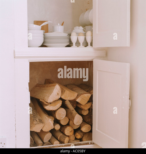 Open kitchen storage cupboards containing fire wood and crockery - Stock-Bilder