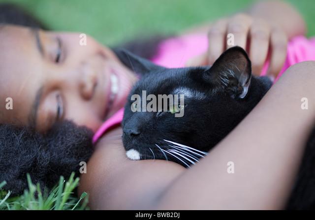 Girl cuddling cat - Stock Image