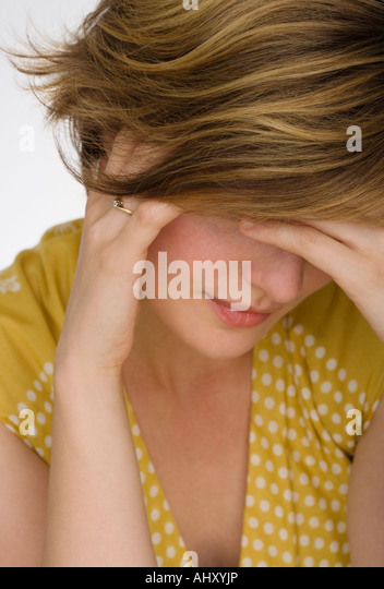 Close up of woman with head in hand - Stock Image