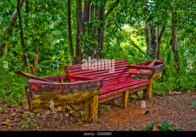 A bench made with a canoe and broken oars. - Stock Image