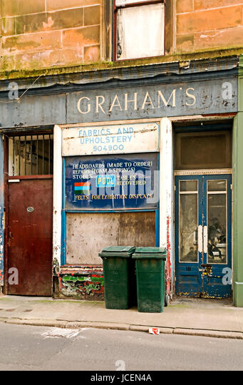 This upholstery shop has closed down and the shop front is badly decayed. - Stock Image