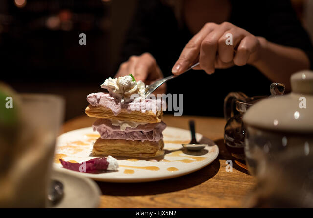 Midsection Of Woman With Cake While Sitting At Restaurant - Stock Image