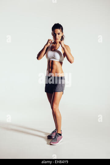 Strong young woman doing boxing exercising in studio. Image of fit young female boxer against grey background. - Stock Image