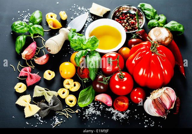 Italian ingredients - pasta, vegetables, spices, cheese - on dark background - Stock Image