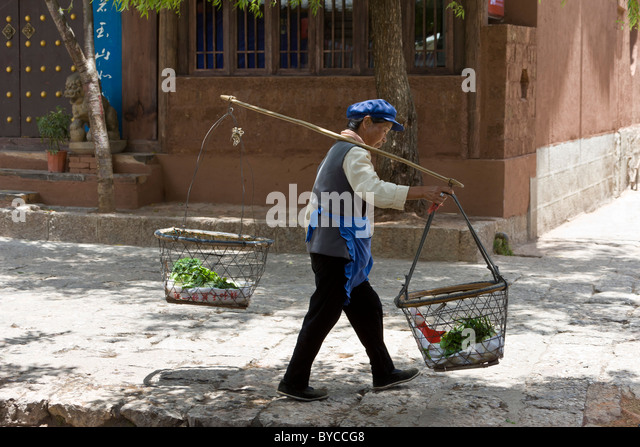 Chinese woman carrying produce in baskets balanced on pole over shoulder in Lijiang old town, Yunnan Province, China. - Stock Image