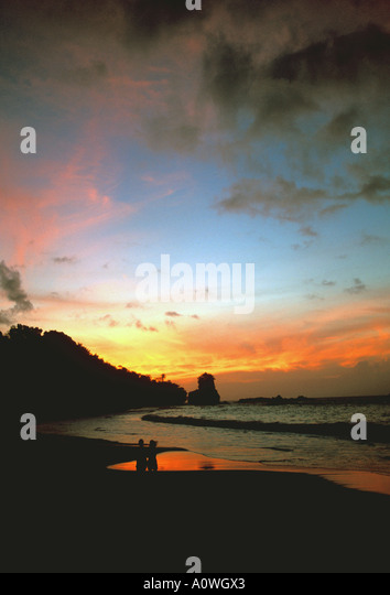 Tropics sunset couple standing on beach - Stock Image