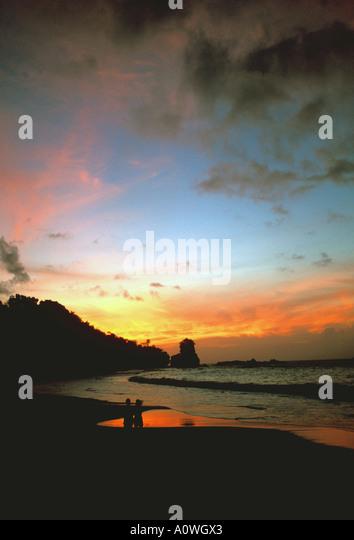 Tropics sunset couple standing on beach - Stock Image