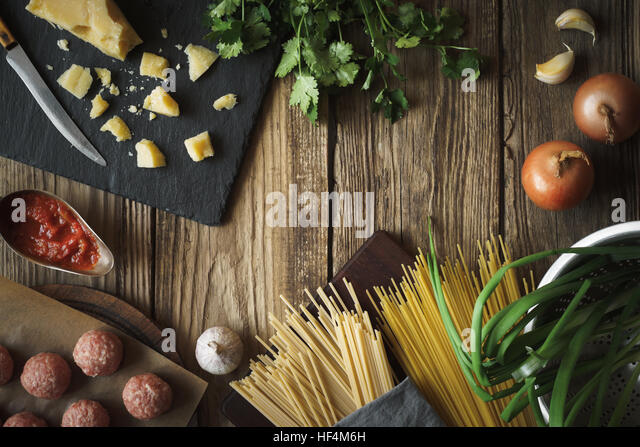 Ingredients for cooking spaghetti, meatballs with cheese and fresh herbs horizontal copy space - Stock Image