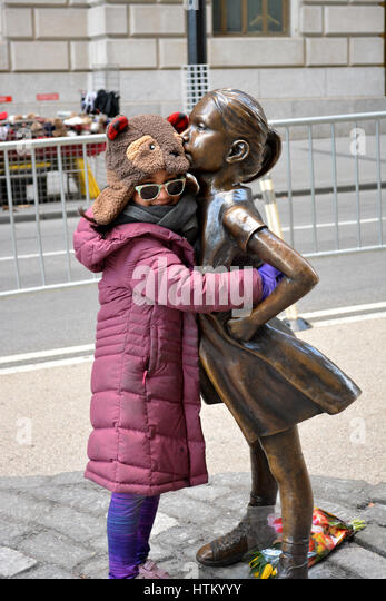 Young girl hugging 'The Fearless Girl' statue in Lower Manhattan. - Stock Image