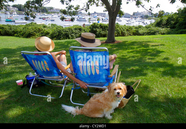 Massachusetts Cape Cod Harwich Wychmere Harbor harbour park boats tree woman lawn chair dog pet - Stock Image
