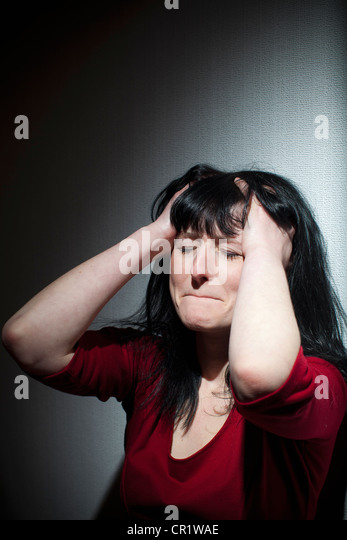Crying woman clutching her head - Stock Image