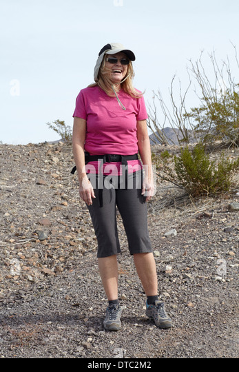 Portrait of senior female hiker on arid hill - Stock Image