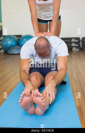 Trainer assisting man with stretching exercises at fitness studio - Stock Image