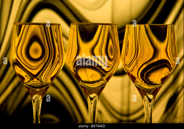 Close up of three wine glasses with a background of gold and black swirling lines reflected in each glass. - Stock Image