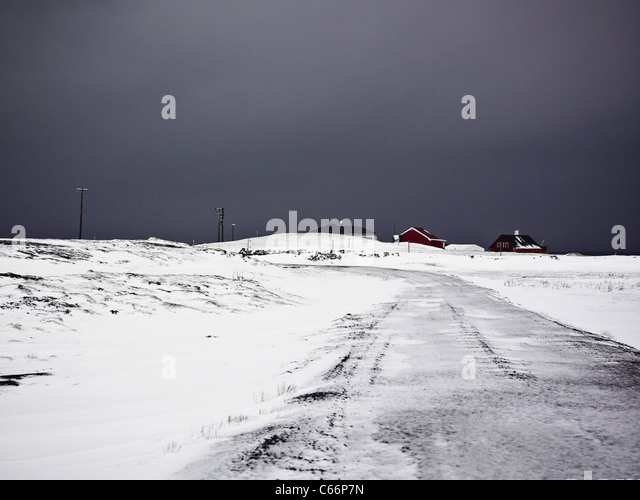 Houses on snowy rural road - Stock Image