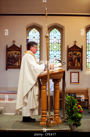 Catholic priest celebrates mass in a church, London, England, UK - Stock Image