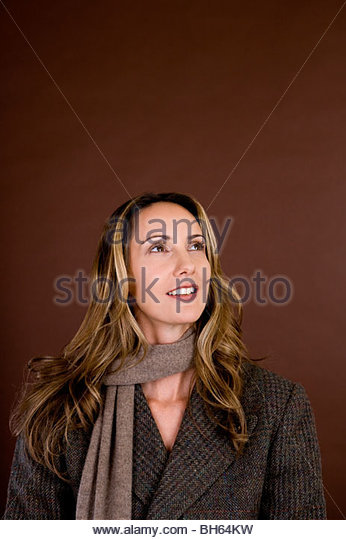Portrait of a mid adult woman wearing an autumnal scarf and jacket - Stock Image