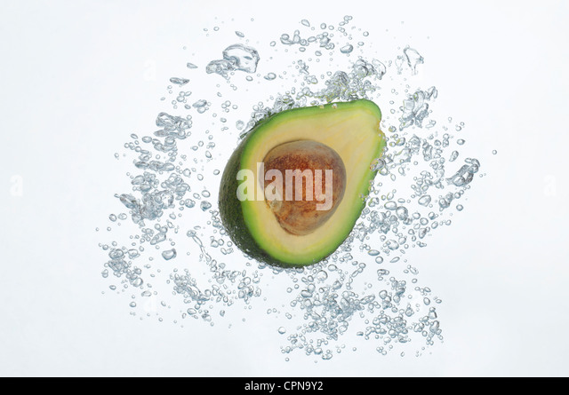 Avocado half submerged in sparkling water - Stock Image
