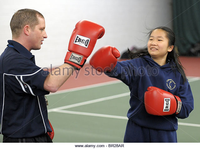 A secondary school pupil takes part in a boxing session. - Stock Image