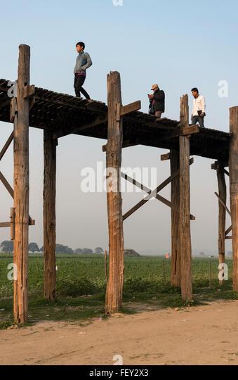 People cross U Bein Bridge - the longest teakwood footbridge in the world, Amarapura near Mandalay, Burma (Myanmar) - Stock-Bilder