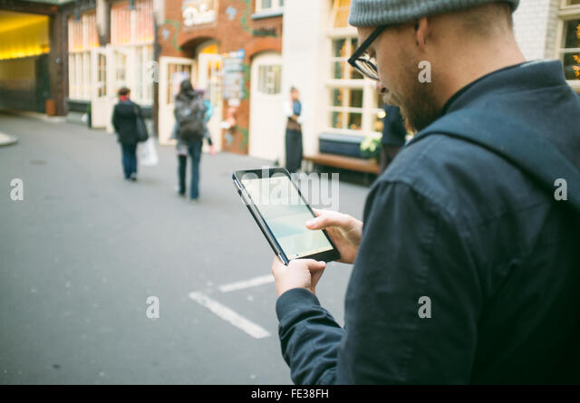 Mid Adult Man Using Digital Tablet On Street - Stock Image