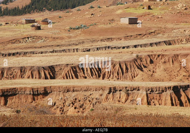 Water erosion on red clay hills in Lesotho Africa - Stock Image