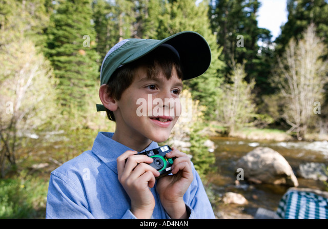 A young boy holding a disposable camera by a river - Stock-Bilder